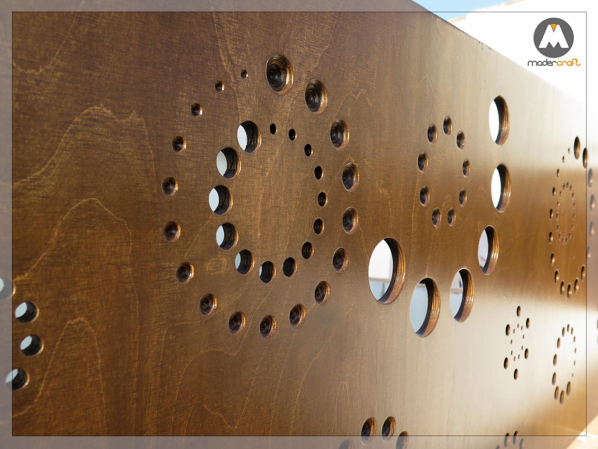 Celosía de madera para exterior de diseño, con círculos que proyecta unas sombras que hacen recordar a las galaxias